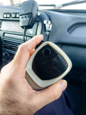 The hand of a policeman holds the tangent of a radio station. Inside the company car. 免版税图像