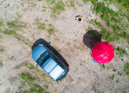 Top view of a car, barbecue made of stones and a parasol in the summer. Camping aerial photography.
