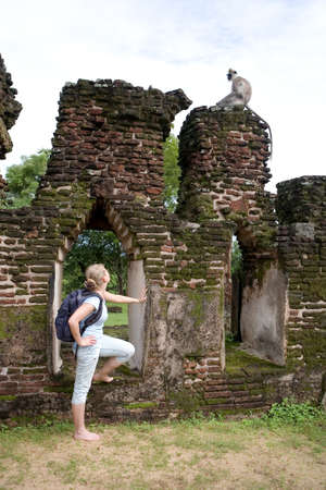A blonde traveler without shoes looks at a wild monkey among the ancient ruins. Polonnaruwa in Sri Lanka.