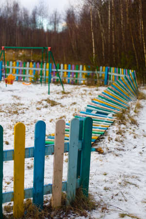 Fallen multi-colored fence of a playground at the edge of the forest. Winter in central Russia. 免版税图像 - 148038471