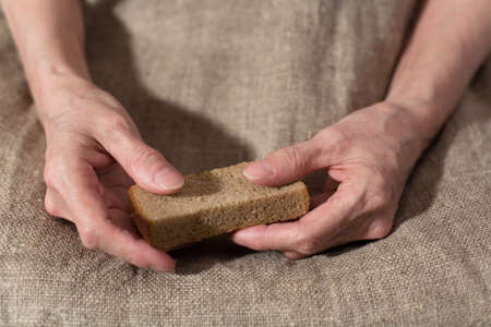 Senile hands hold a slice of rye bread. Close-up.