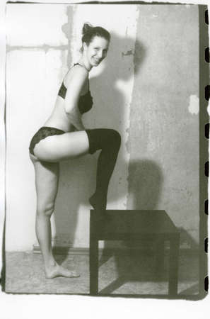 A young slender girl in lingerie puts a stocking on her leg. Attention! Image contains grit and other artifacts of analog photography!