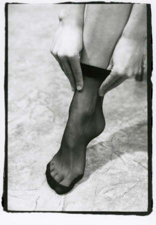 A girl puts on a black sock on her leg close-up. Attention! Image contains grit and other artifacts of analog photography!