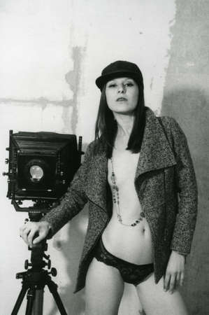 A half-naked girl stands next to a large format retro camera. Attention! Image contains grit and other artifacts of analog photography! 免版税图像 - 148137038
