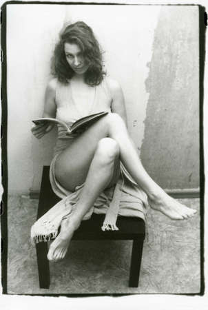 Black and white photo of a girl with bare legs and a book in her hands. Attention! Image contains grit and other artifacts of analog photography! 免版税图像 - 148137338