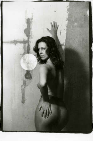 A girl in pantyhose on her naked body turned her ass to the viewer. Attention! Image contains grit and other artifacts of analog photography!