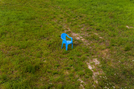 There is a lonely plastic chair in the meadow. Summer. Reklamní fotografie