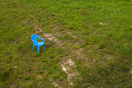 There is a lonely plastic chair in the meadow. Summer. 免版税图像 - 153383457