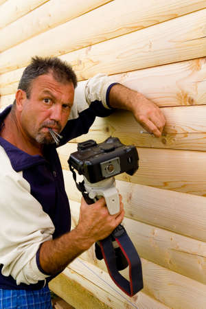 A man hammers nails with a camera. Portrait and humor. Reklamní fotografie