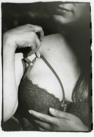 Women's fingers gracefully hold the bra strap. Attention! The image contains grain and other analog photography artifacts!