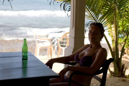 A girl in a swimsuit sits at a table against the backdrop of the ocean. Rest at the resort. Reklamní fotografie