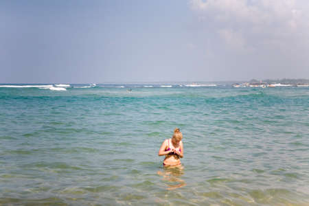 A girl in a swimsuit is standing in the ocean. Rest at the resort. 免版税图像 - 155538692