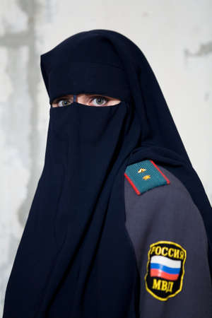 Girl in niqab and uniform of a Russian policeman. People.