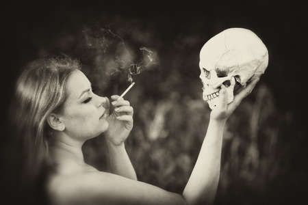 A beautiful girl with a cigarette holds a human skull in her hand. Health and bad habits. Reklamní fotografie