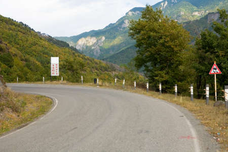 A turn of the mountain road and a signpost with the name of the village of Khulo. Landscape of Georgia.