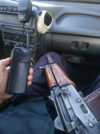 A policeman with a assault rifle and a radio station sits in a car. Armament. Reklamní fotografie