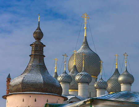Domes of the Rostov Kremlin in the winter against the sky with easy clouds
