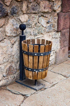 garbage can in wooden registration at a stone wall