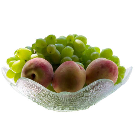 Green grape and peaches isolated on white.
