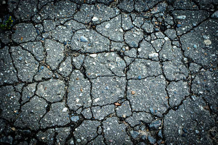 Background with old asphalt pavement in cracks Фото со стока