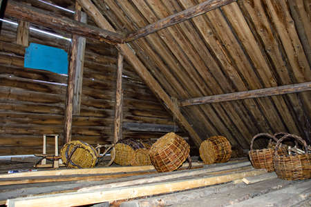 Wicker baskets under the roof of a wooden house