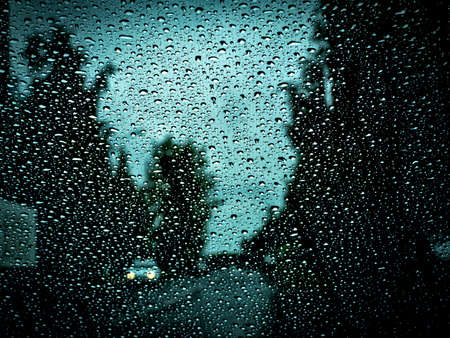 view from the windshield of a car covered with raindrops