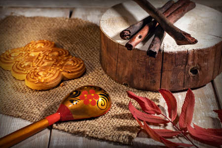 cookies, spoon with a pattern and cloth on a wooden table