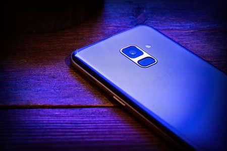 blauwe mobiele telefoon op een houten achtergrond