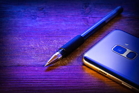 pen and blue mobile phone on a wooden background