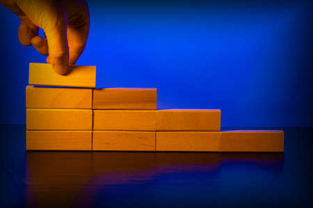 Hand stacking wooden blocks in the form of stairs. Business concept for process growth success. Stockfoto