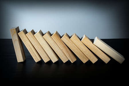 A wooden block stops the fall of other parts of the domino effect. Business risk management concepts. Stockfoto