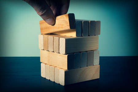 A hand places wooden blocks in a stack. Business concept for process growth success.