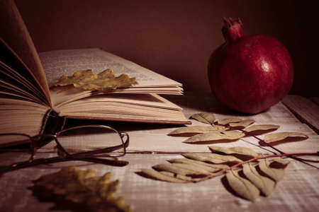 Open book, glasses, pomegranate and autumn leaves on a wooden table. Autumn still life. Stockfoto
