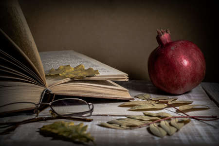 Open book, glasses, pomegranate and autumn leaves on a wooden table. Autumn still life. Standard-Bild