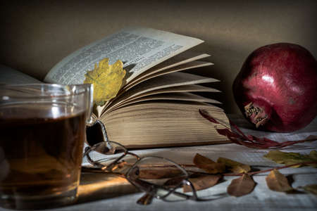 Open book, tea, glasses, pomegranate and autumn leaves on a wooden table. Autumn still life.