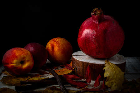 Autumn still life with pomegranate, nectarines and fallen leaves on a wooden background Banque d'images - 131766287
