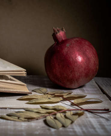 Open book, pomegranate and autumn leaves on a wooden table. Autumn still life.