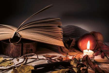 Boek, glazen, fruit, een brandende kaars en herfstbladeren op een houten tafel. Herfst stilleven. Stockfoto