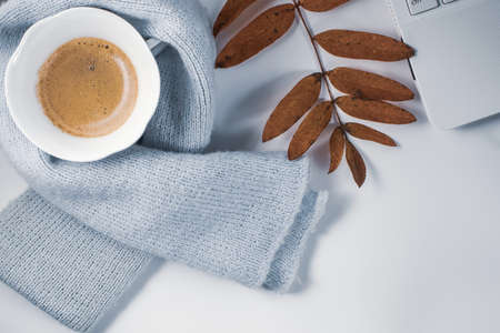A cup of coffee with foam, a white laptop, a scarf, glasses, a pen and autumn leaves on a white background. Autumn mood.
