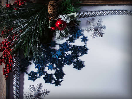 Christmas background with fir branches, cones, a bunch of red berries, candles and snowflakes.
