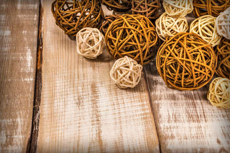 decorative rattan balls of different sizes lie on a light wooden surface Stockfoto