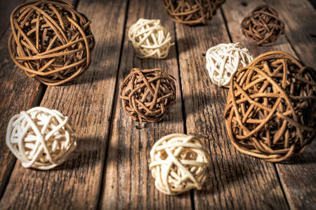 Dark and light decorative rattan balls of different sizes lie on a wooden surface Stockfoto