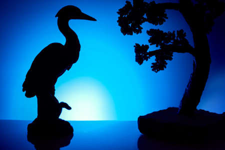 Silhouette of a bird and bonsai tree against blue background.