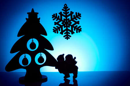 Silhouettes of Christmas tree, snowflakes and children on a blue background. Imagens