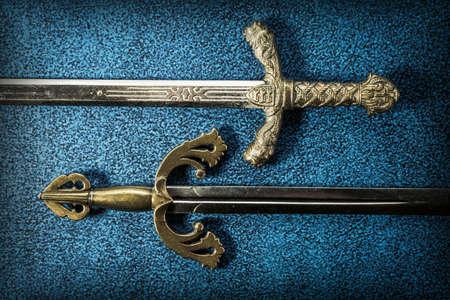 Deux poignées d'épées chevaleresques en gros plan sur un fond bleu foncé. Vue d'en-haut Banque d'images