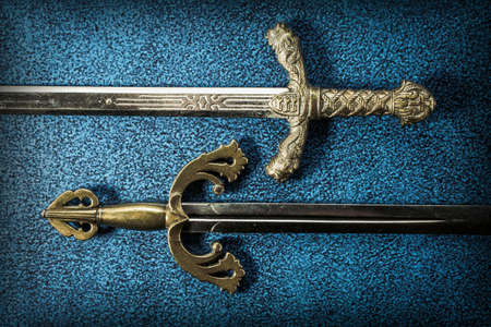Two hilt of knightly swords close-up on a dark blue background. View from above