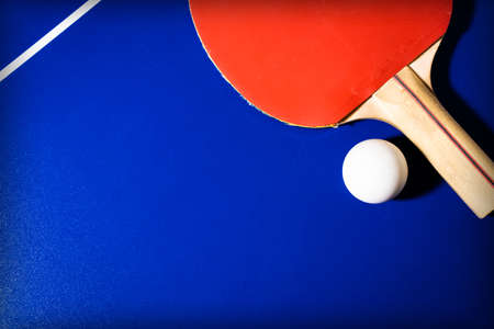 Red racket and ball for table tennis on a blue table background