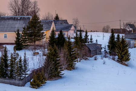 Beautiful winter landscape with a small village on a hill against the backdrop of a sunny sunset in the cloudy sky. Russia, Arkhangelsk region Stock Photo