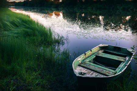 Tranquil morning landscape with river bank and old fishing boat at sunrise