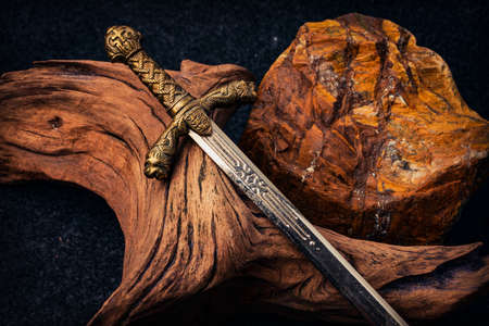Knight's sword on the background of an old textured wooden driftwood and a rough stone of brown color